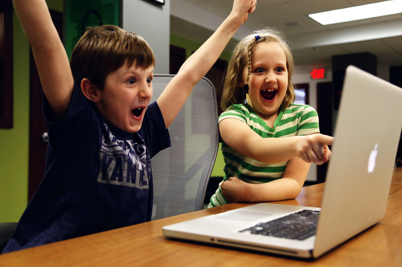 Photo showing two kids excited in front of a laptop